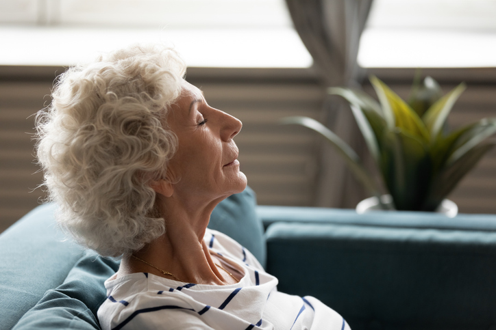 Senior woman relaxing on sofa with eyes closed
