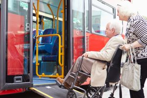 Old man on wheelchair going up a bus assisted by his wife