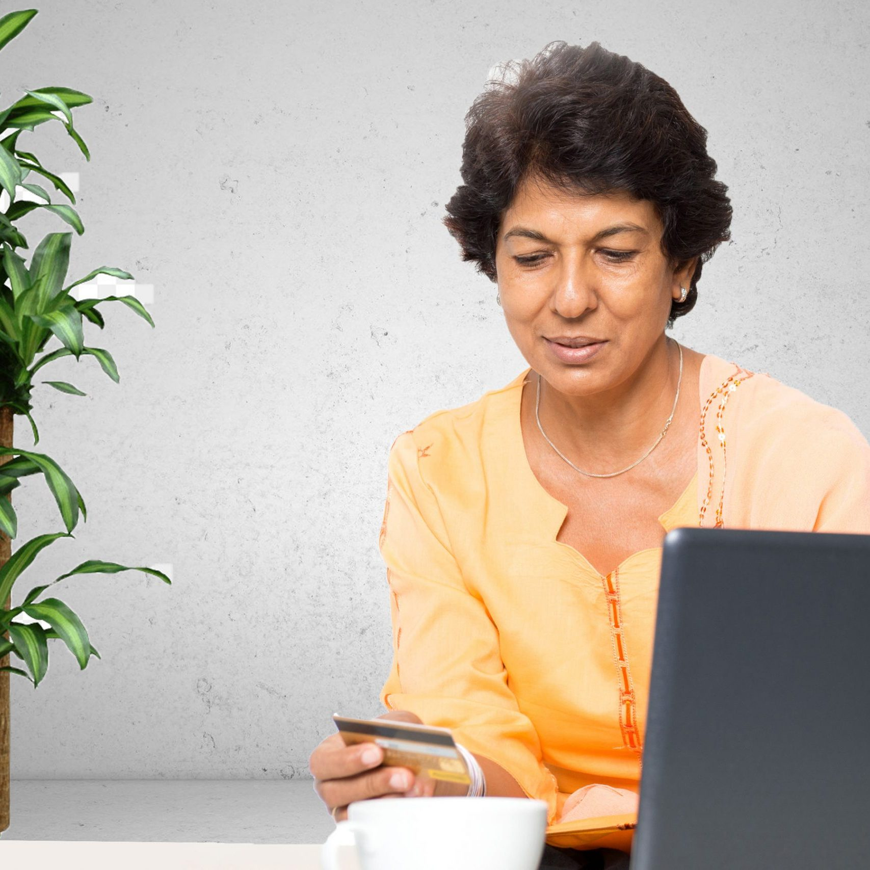 An elderly woman holding a credit card at her computer
